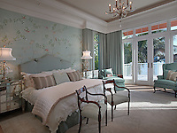 This romantic master bedroom suite features hand painted silk wallcovering, custom upholstered bedding and antique mirror nightstands.