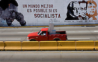 "A truck passes by a wall painting with the faces of Venezuelan President Hugo Chavez, Venezuelan independence heros Francisco de Miranda and Simon Bolivar and guerilla lider Che Guevara with a phrase reading ""a better world is possible, if it's socialist"" in Caracas, Venezuela, on Saturday, Jul. 08, 2006. (ALTERPHOTOS/Alvaro Hernandez)"