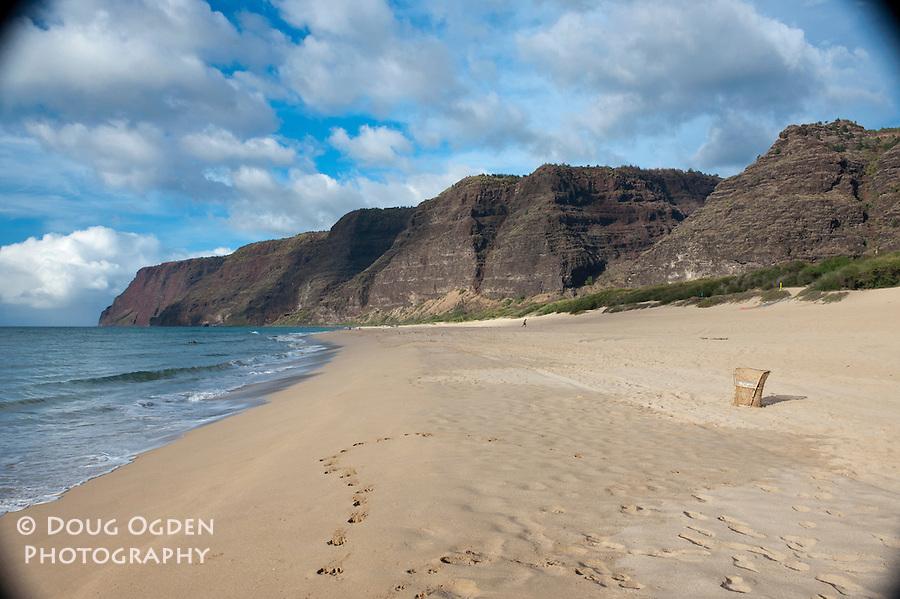 A wicker chair sits solitary on Barking Sand Beach, Polihale SP, Na Pali coast in the distance, Kauai, Hawaii