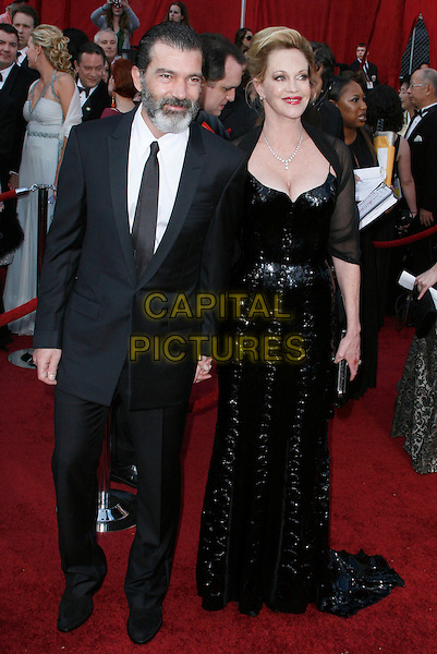ANTONIO BANDERAS & MELANIE GRIFFITH.The 82nd Annual Academy Awards held aat The Kodak Theatre in Hollywood, California, USA..March 7th, 2010.oscars full length black suit jacket beard facial hair married husband wife dress sequins sequined sheer wrap clutch bag maxi .CAP/EAST.©Eastman/Capital Pictures.