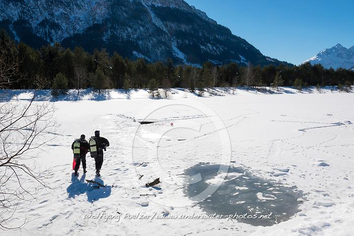 Taucher auf dem See auf dem Weg zum Eisloch, Eistauchen, scuba on the way to the ice hole, scuba icediving, Lechausee, Reutte, Weissenbach, Tirol, Oesterreich, Tyrol, Austria, MR Yes
