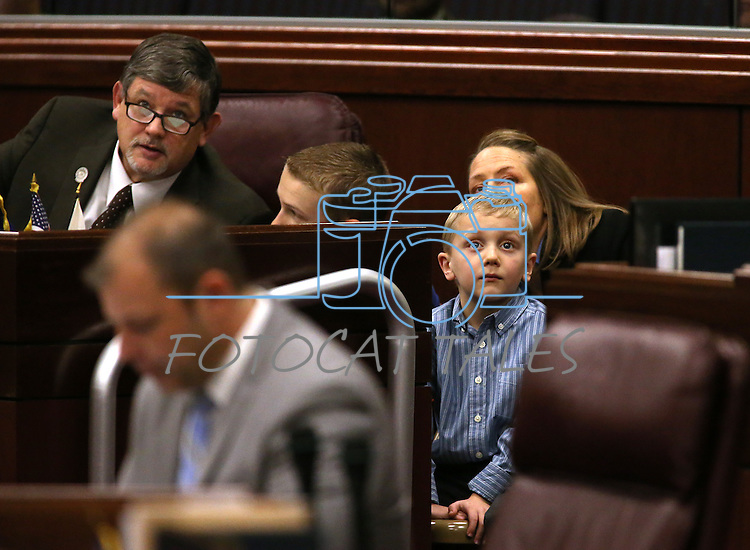 Nevada Assemblyman James Oscarson, R-Pahrump, watches votes tally on the big screen on the Assembly floor with guests, the Sever family, at the Legislative Building in Carson City, Nev., on Tuesday, March 3, 2015. <br /> Photo by Cathleen Allison