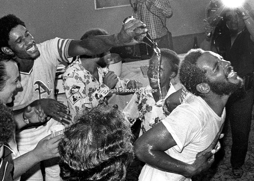Oakland A's celebrate AL Division win in  1975, Claudell Washington dumps champane on the back of Billy North..youngster in the center is A's clubhouse boy, Stanley Burell (Ak M.C. Hammer)<br />