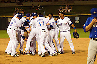 Round Rock Express players mob shortstop Luis Hernandez as they celebrate a walk off win in the Pacific Coast League against the Las Vegas 51s on August 7th, 2012 at the Dell Diamond in Round Rock, Texas. Hernandez delivered the game winning hit in the bottom of the ninth inning as the Express defeated the 51s 5-4. (Andrew Woolley/Four Seam Images)..