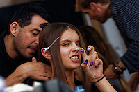 A model shows her claws as she is prepared for the catwalk during fashion week. photo by Trevor Collens