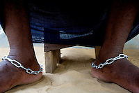 """a  """"trokosi"""" religious slave wears chains around his ankles while  performing a pagan traditional ritual in one of the shrines of Atito in the Volta region, Ghana on Saturday March 10 2007.."""