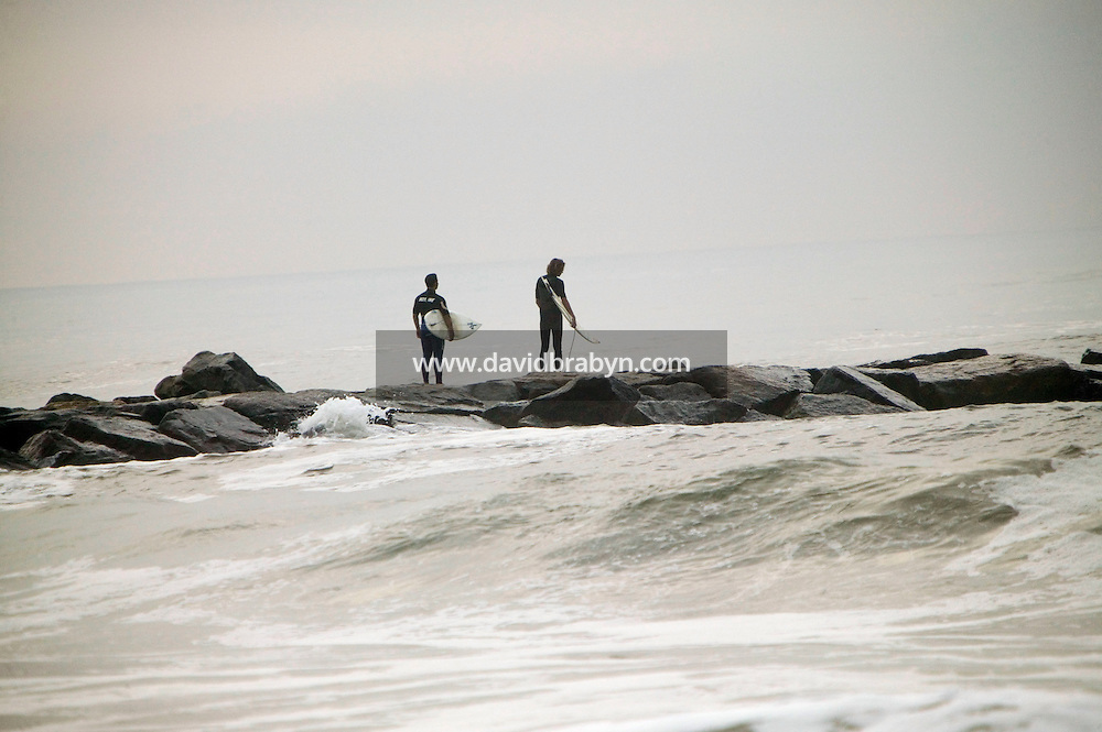 Two surfers walk out on the jetty at Far Rockaway beach in New York, United States, in the early morning of 17 September 2005. Photo Credit: David Brabyn.