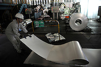 A worker folds a steel plate at Shanghai Baosteel factory. Baosteel is the largest Chinese iron and steel conglomerate. It is a state-owned enterprise, headquartered in Shanghai..