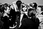 Supporters of Senate Majority Leader Harry Reid, D-Nev., take photos of themselves with Michelle Obama magazine covers as they wait for first lady Michelle Obama to speak at the Get Out The Vote rally at Canyon Spring High School in North Las Vegas on Nov. 1, 2010.
