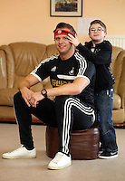 Pictured: 10 year old James Morris (R) helps Swansea City FC ambassador Lee Trundle (L) to put on his red Comic Relief headband. Monday 17 March 2014<br /> Re: Swansea City FC Ambassador, Lee Trundle has visited The Play and Leisure Opportunities Library (PLOL) to see how Comic Relief money is making a difference to vulnerable people in Swansea. The PLOL provides play sessions for children and adults with profound disabilities. A small Comic Relief grant has allowed the group to purchase and cover the insurance cost of sensory toys which they loan to families