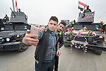 Two residents of Mosul celebrate the partial liberation of their city from control by the Islamic State group by taking a selfie on January 27, 2017, in front of festooned army vehicles. Although a portion of the city has been liberated from ISIS, fierce fighting is predicted as the army moves to retake the remainder of the city.