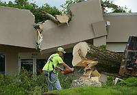 NWA Democrat-Gazette/BEN GOFF @NWABENGOFF<br /> Josh Pangle of Pangle's Tree Service, based in Bentonville, helps remove a large hackberry tree Friday, May 19, 2017, with help from Oelke Construction Company, after it fell on a building at Beau Terre Office Park in Bentonville. Multiple trees in the office park were broken or downed after an overnight storm passed through the area.