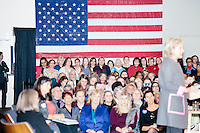 People listen as Democratic presidential candidate and former First Lady and Secretary of State Hillary Rodham Clinton speaks at the Women's Economic Opportunity Summit at Southern New Hampshire University in Hooksett, New Hampshire.