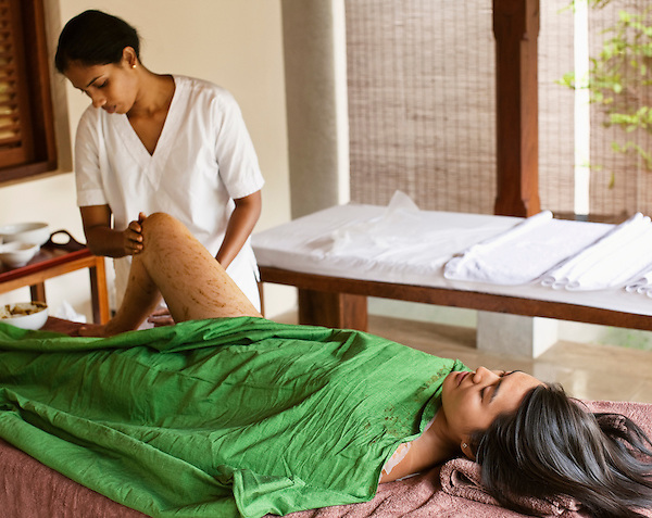Young woman receiving an Aloe and Honey Herb body wrap, part of the 135-minute  Sahana Coconut Skin Treat spa treatment at Sahana Spa, Saman Villas, Aturuwella, Bentota, Sri Lanka.