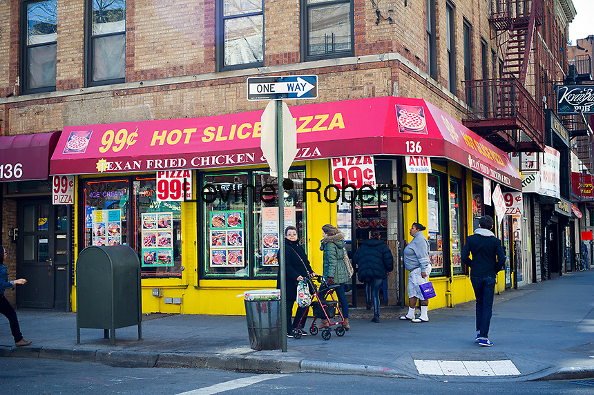 A pizza restaurant in Brooklyn in New York advertises its 99 cent slice on Saturday, April 7, 2012. 99 cent slice pizza joints have been appearing as lunch prices are coming down due to the recession. Bon Appetit. (© Frances M. Roberts)