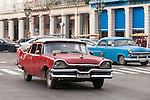Havana, Cuba; a classic red 1950's Plymouth serves as a taxi along the Paseo de Marti