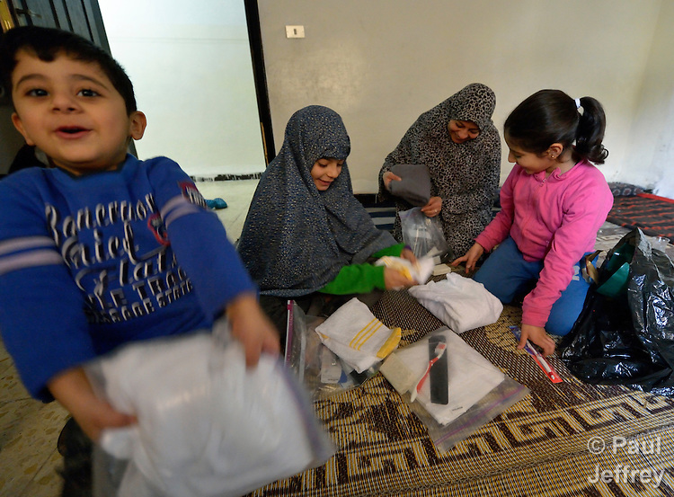 Souad Kasem Issa and her children Nour Eddin, 5, Rawan, 10, and Rahaf, 9, open hygiene kits provided by International Orthodox Christian Charities. They are Syrian refugees living in Amman, Jordan. The family of eight fled the city of Homs as fighting there worsened in 2012. Their home in Syria has since been destroyed by bombing, and they are struggling to survive in Jordan's capital city. The IOCC is a member of the ACT Alliance. The hygiene kits include a towel, soap, toothbrush, comb, and other items.
