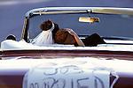 "groom rests his head on bride's sholder. ""Just married"" sign on back of car"