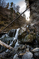 As the sun ascends in the spring sky, it crosses the ravine that houses Pioneer Falls in the Chugach Mountains near Palmer, Alaska.