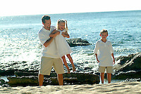 Dad playing with daughter and son at the beach while on vacation in Hawaii