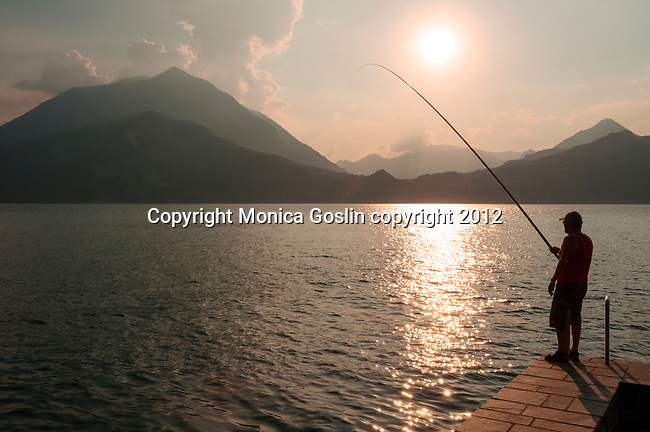 Local man fishing on Lake Como at sunset