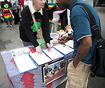 Signing a petition. Protests are held in London every Saturday for democratic chnage in Zimbabwe. This set is from September 2007. Protests against Robert Mugabe, London, England