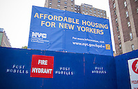 A sign announcing the construction of affordable housing is seen in the the New York nieghborhood of Chelsea on Sunday, August, 8, 2010. The city is building new housing on the sites of parking lots in existing housing projects. (© Richard B. Levine)