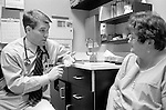 Young male doctor in discussion with middle age female patient in examination room