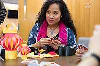 Karonika Brown, 34, plays UNO before a Lunar New Year celebration in the Asian American Connections Center at Middlesex Community College in Lowell, Mass., USA, on Thurs., Feb. 15, 2018. Brown graduated with a degree with an Associates Degree in Liberal Arts and Sciences from Middlesex Community College in 2016, and continues to take classes there and work as a writing tutor for other students. Brown is an immigrant from Cambodia. The Asian American Connections Center was established at the school using a federal grant in 2016 and serves as a focal point for the Asian community at the school, predominantly Cambodian, to gather, socialize, study, and otherwise take part in student life.