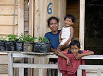 In this 2007 photo, Rusmiati and her two children at her home in Lhok Me, in Indonesia's Aceh province. Rusmiati was left homeless by the 2004 tsunami, but YEU, a member of the ACT Alliance, worked with the village to build new houses in a safer area, as well as help revitalize their income generating activities. Her children are Fathan, 3, and Rahmat, 8. The tsunami killed 221,000 people in Aceh province and left more than 500,000 displaced.<br /> <br /> Compare this photo with 2014 image of her in same spot with these two children and one more born in th interim.<br /> <br /> <br /> <br /> In Blang Ulam, Aceh, survivors of the 2004 tsunami are living in new homes constructed by CD Bethesda/YAKKUM Emergency Unit and the ACT Alliance.