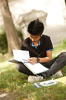 Montreal (Qc) CANADA - August 19 2009 - model released photo - asian (Filipino) male teen student does his homework outdoor in an Old-Montreal park