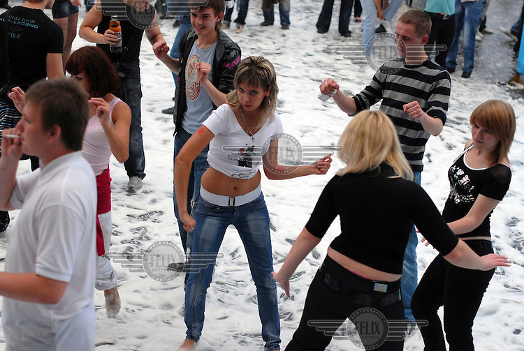 People dance on beer froth at a beer festival held at a stadium on the outskirts of Moscow.