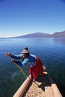 Female boater using pole to push reed boat at the Floating Islands of Uros, Lake Titicaca, Peru