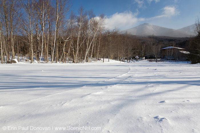 Franconia Notch State Park - Flume Visitor Center during the winter months in the White Mountains, New Hampshire USA. Off in the distance, strong winds blow snow and clouds over Mount Liberty.