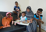 Mekiya Kebir and her children, recently arrived refugees from Eritrea, explore a book in their apartment in Lancaster, Pennsylvania. They got the book and other educational materials from Church World Service, which resettles refugees in Pennsylvania and other locations in the United States. <br /> <br /> Photo by Paul Jeffrey for Church World Service.