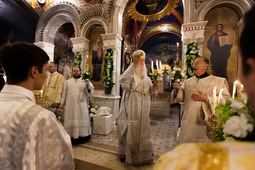 Switzerland. Geneva. Easter at the Russian Church. The church is a lovely 19th-century Russian Orthodox church and designed in a Byzantine Moscovite style. The church's full name is Cathédrale de l'Exaltation de la Sainte Croix. The Archbishop Michael with his mitre during the religious service on the night of Easter Sunday. The Archbishop Michael makes the sign of the cross with the censer and blesses a crowd of believers. He holds in his left hand the Paschal Trikirion which is a liturgical triple-candlestick used at Easter time in the Eastern Orthodox ceremony. It is used from the commencement of the celebration of the Resurrection during the Paschal Vigil. The nighttime liturgy is a blessing of Easter fire with candles and the celebration of the Easter Proclamation of the Resurrection of Jesus Christ. A large religious painting on the nave's wall represents God the Father. In mainstream trinitarian Christianity, God the Father is regarded as the first person of the Trinity, followed by the second person God the Son (Jesus Christ) and the third person God the Holy Spirit. Other paintings of Jesus Christ and the Virgin Mary. Archbishop Michael (Secular name - Simeon Vasilyevich Donskoff; born on 29 March 1943) is a bishop of the Russian Orthodox Church Outside of Russia, Archbishop of Geneva and Western Europe. Easter, also called Pascha or Resurrection Sunday is a festival and holiday celebrating the resurrection of Jesus from the dead, described in the New Testament as having occurred on the third day of his burial after his crucifixion.The Russian church serves not only the Russian community but also Bulgarians, Serbs, Coptic Christians and other Orthodox worshippers who do not have their own church in Geneva. 16.04.17 © 2017 Didier Ruef