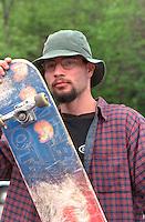 Bearded alternative man age 22 posing with skateboard. Cinco de Mayo St Paul  Minnesota USA