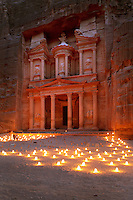 Treasury of the Pharaohs or Khazneh Firaoun, 100 BC - 200 AD, Petra, Ma'an, Jordan. Originally built as a royal tomb, the treasury is so called after a belief that pirates hid their treasure in an urn held here. Carved into the rock face opposite the end of the Siq, the 40m high treasury has a Hellenistic facade with three bare inner rooms. Petra was the capital and royal city of the Nabateans, Arabic desert nomads. Nighttime view with candles lighting up the plaza and man showing huge scale of the edifice. Picture by Manuel Cohen