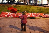 Roma, 28 Febbraio 2013.Piazza San Giovanni Bosco Per ricordare Roberto Scialabba, giovane del quartiere ucciso dai fascisti il 28 Febbraio 1978..A fine corteo vengono deposti fiori sulla targa dove uccisero Roberto e lanciate in aria lanterne rosse, 35, gli anni passati dalla  sua morte..Una bambina gioca con la bandiera rossa