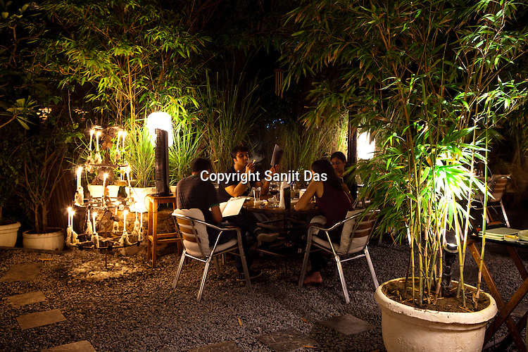 Guests enjoy the surroundings of  Magique, a restaurant cum lounge shrouded in lush greenery and lit with hundreds of tea-light candles located in the south of New Delhi, India. Photograph: Sanjit Das/Panos