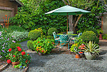 Vashon-Maury Island, WA: Summer patio encircled with summer pots of red geraniums, nasturtiums and yucca set in a cottage garden