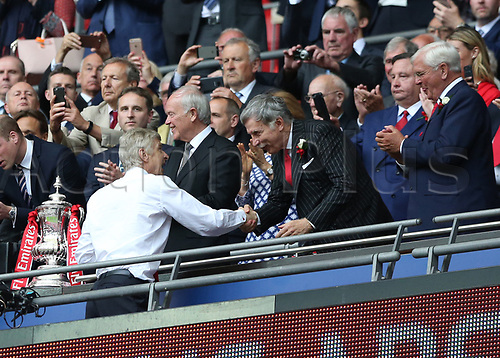 May 27th 2017, Wembley Stadium, London England;  FA Cup Final, Arsenal versus Chelsea FC; Arsenal Manager Manager Arsene Wenger shakes hands with Arsenal's largest stakeholder Stan Kroenke from the stands after collecting an FA Cup winners medal from HRH Prince William, Duke of Cambridge after defeating Chelsea by 2-1