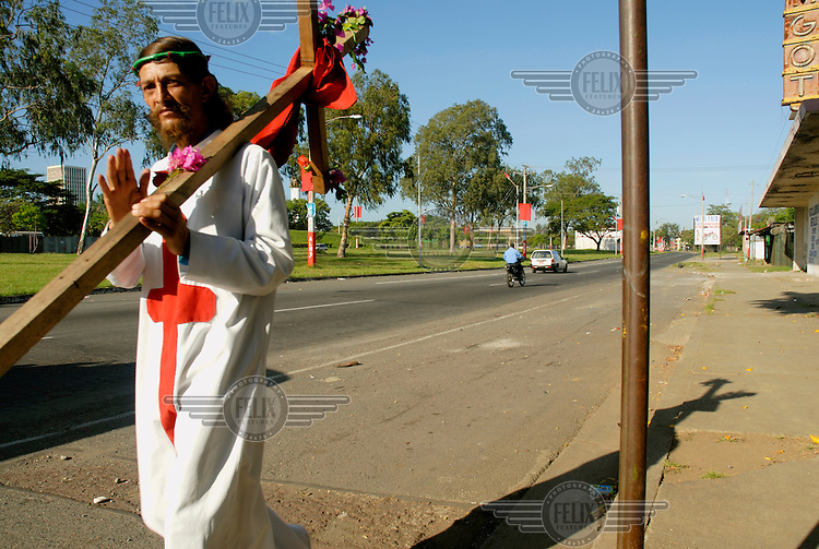 A long-haired man dressed as Jesus Christ carries a crucifix through the streets of Managua. ..Photo: Dermot Tatlow/Panos Pictures/Felix Features
