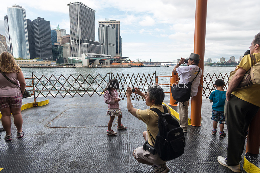 New York, USA, Tourists taking pictures on the Staten Island Ferry as it approaches South Ferry, in Manhattan, after a 5.2 mile voyage across Upper New York Bay, from St George, Staten Island. ©Stacy Walsh Rosenstock