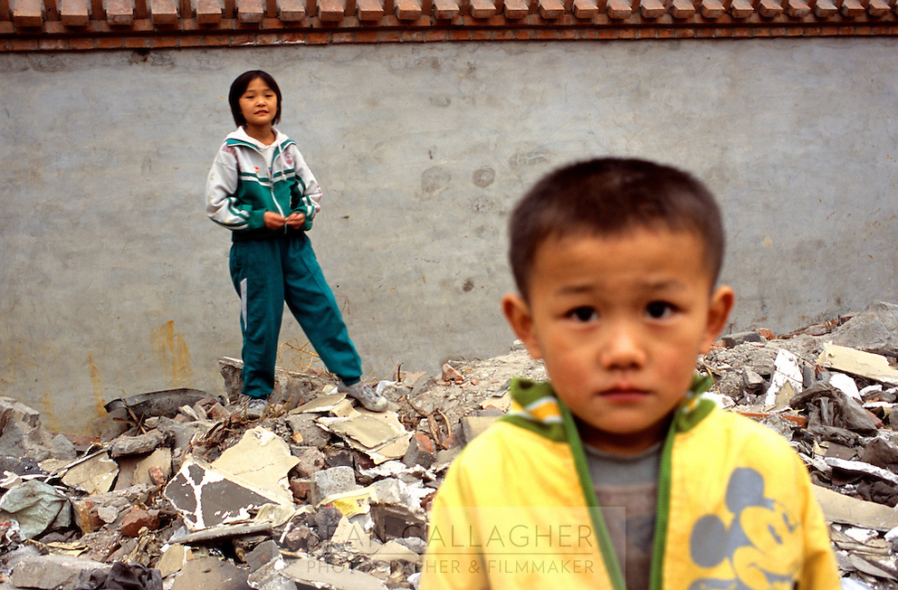 CHINA. Beijing. Children play in the ruins of an old hutong (traditional home) in the central Qianmen district, destroyed to make may for new developments aimed at modernising the city for the 2008 Summer Olympics. 2005