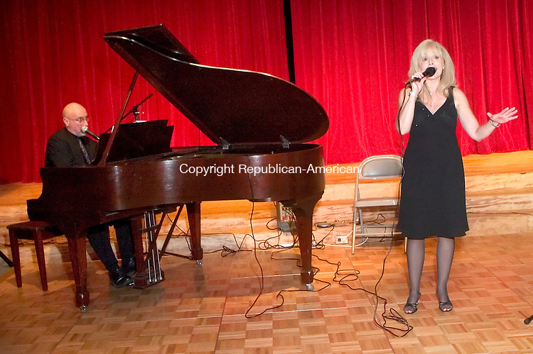 WATERBURY, CT- 07 SEPT 06- 0907006JT10-<br /> Claudia Hughes, right, sings as she's accompanied by pianist Frank Pisani at the Mattatuck Museum Arts &amp; History Center for the center's &quot;First Thursday,&quot; to celebrate its members and the arts and culture in Waterbury. The event featured vocalist Claudia Hughes and pianist Frank Pisani.<br /> Josalee Thrift Republican-American