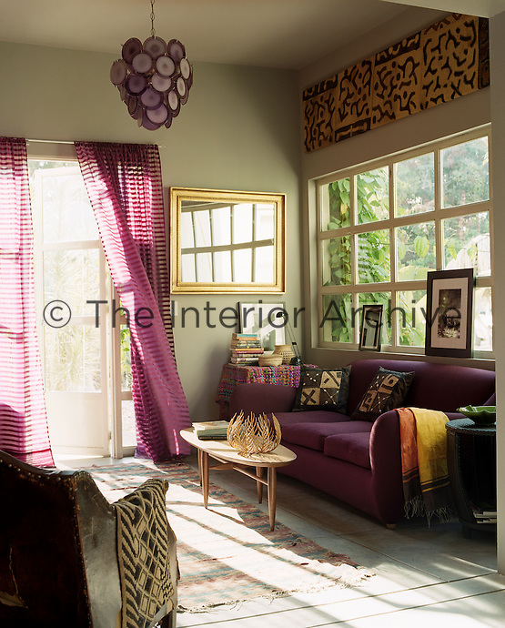 Double doors lead to the garden from a sitting room arranged in an elegant colour scheme of violet and grey