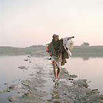 an eldery man crosses a small channel of the ganges on a submerging bridge made of waste, Feb 2014