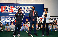 First Lady Michelle Obama and US Soccer Foundation CEO and President Ed Foster-Simeon watch  DC United player Jaime Moreno speak during a US Soccer Foundation clinic held at City Center in Washington, DC.