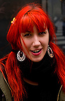 Alternative young woman with bright red hair and earrings in New York City on street